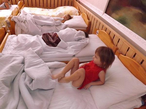 Девочка в красной маечке на кроватке делает упражнения