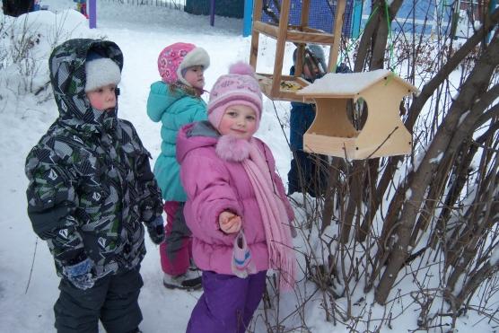 Дети в зимней одежде стоят около птичьих кормушек
