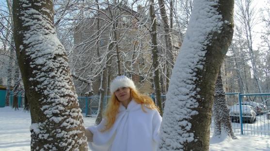 Девушка в костюме Зимушки-зимы стоит между деревьев