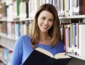 Девушка в синем свитере стоит с раскрытой книгой в библиотеке