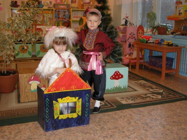 Мальчик стоит рядом с девочкой, которая прячется в картонном домике