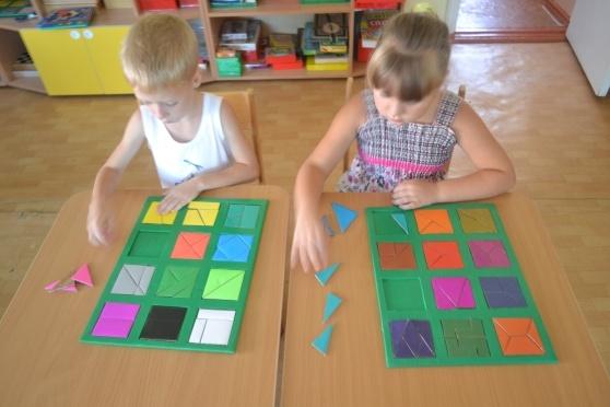 Двое детей складывают квадраты из разных геометрических фигур