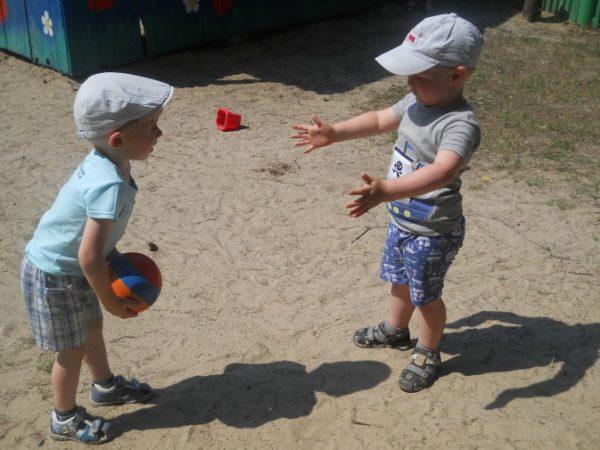 Два мальчика в кепках играют с мячом