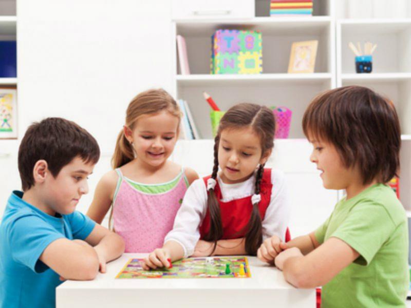Две девочки и два мальчика играют в настольную игру