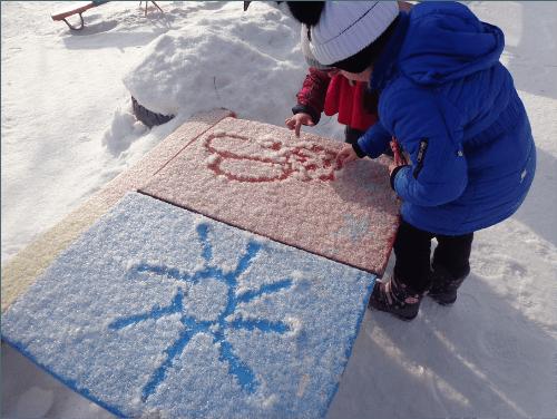 Двое детей рисуют пальцами солнце и цветок на снегу