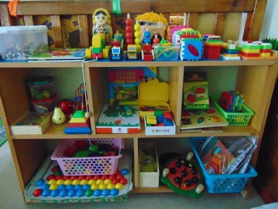 На полках размещены разнообразные игрушки для сенсорного развития