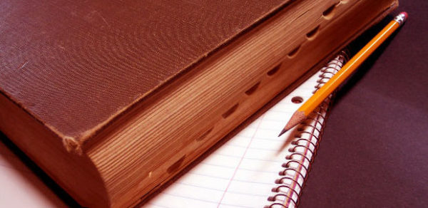 Книга и карандаш лежат на блокноте