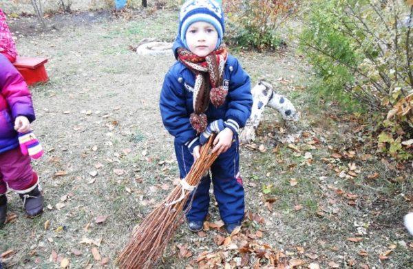 Мальчик подметает осенние листья