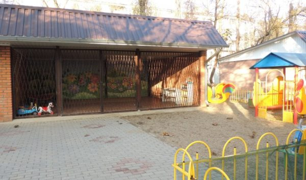 Пустая территория детского сада с огороженной площадкой