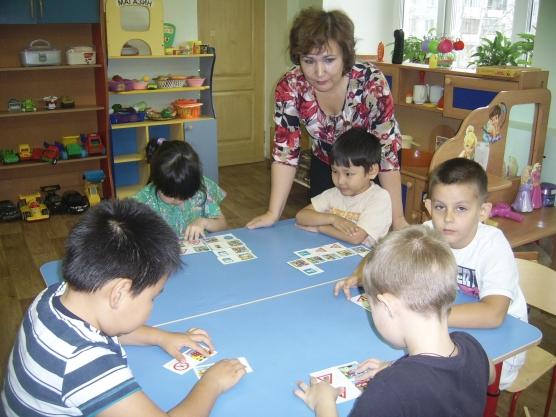 Пятеро детей за столом играют в лото, воспитатель наблюдает