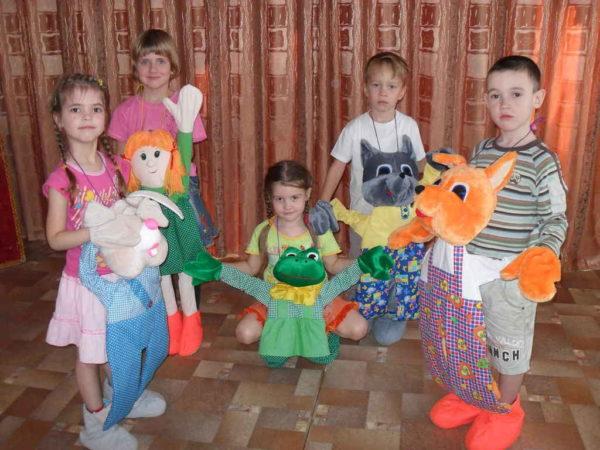Пятеро детей управляют большими куклами-марионетками