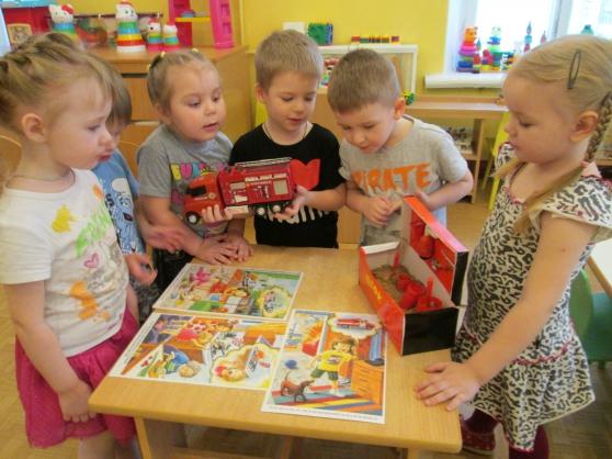 Дети стоят вокруг стола с разложенными на нём картинками, мальчик держит пожарную машину