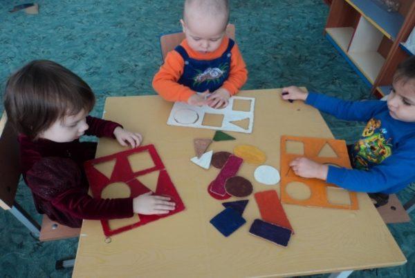 Три ребёнка сидят за столом, у каждого свой набор геометрических фигур
