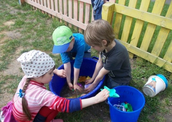 Трое детей моют игрушки на улице