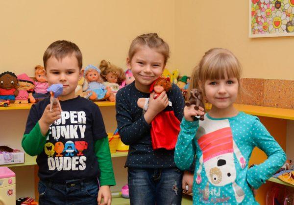 Мальчик и две девочки с игрушками в руках