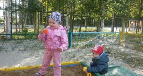 Мальчик и девочка, одетые по-весеннему, играют в песочнице