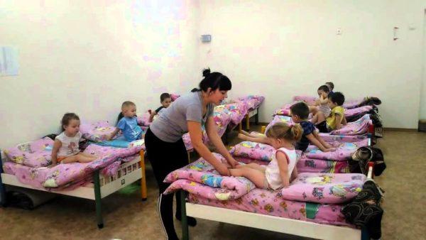 Воспитатель гладит ножки ребёнка