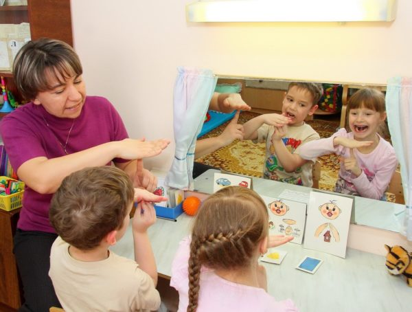 Воспитатель показывает на зеркальном отражении детей, как правильно выполнять упражнение