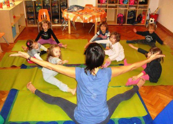 Воспитатель и дети сидят на ковре, разведя руки и ноги в стороны