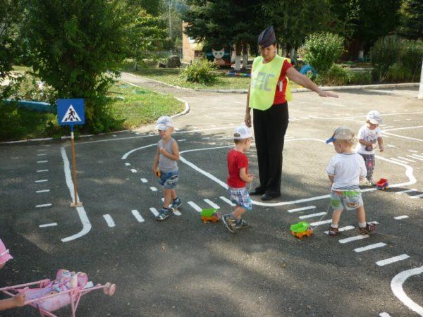 Воспитатель в костюме постового, дети с машинками, на площадке дорожная разметка