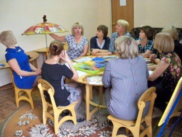 Воспитатели сидят за круглым столом на мастер-классе, педагог в процессе работы указывает на зонт