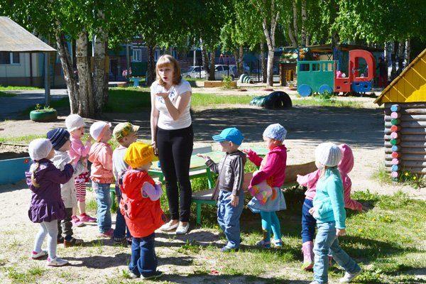 На площадке воспитательница что-то показывает на ладони детям