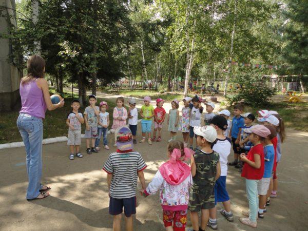 Воспитательница играет в мяч с детьми, стоящими полукругом