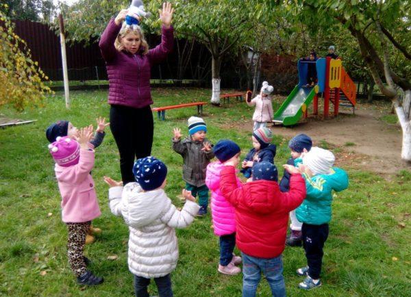 Воспитательница подняла руки вверх, дети в осенней одежде повторяют за ней