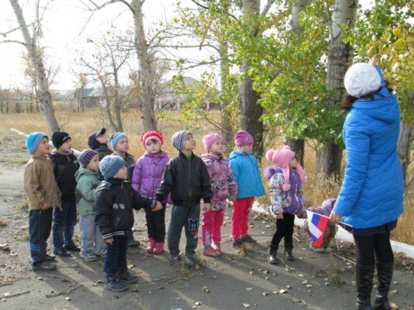 Воспитательница показывает детям листья на осенних деревьях