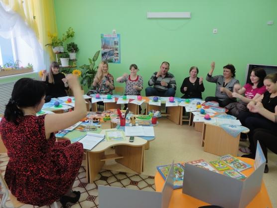 Воспитательница показывает родителям, сидящим по кругу, как выполнять движения рукой