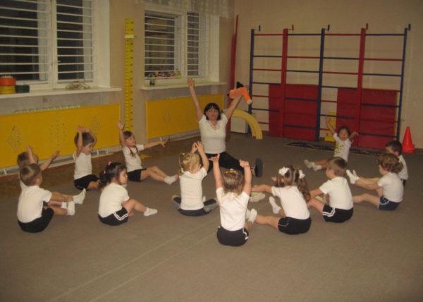 Воспитательница проводит физкультурное занятие в спортзале, дети сидят, вытянув руки вверх