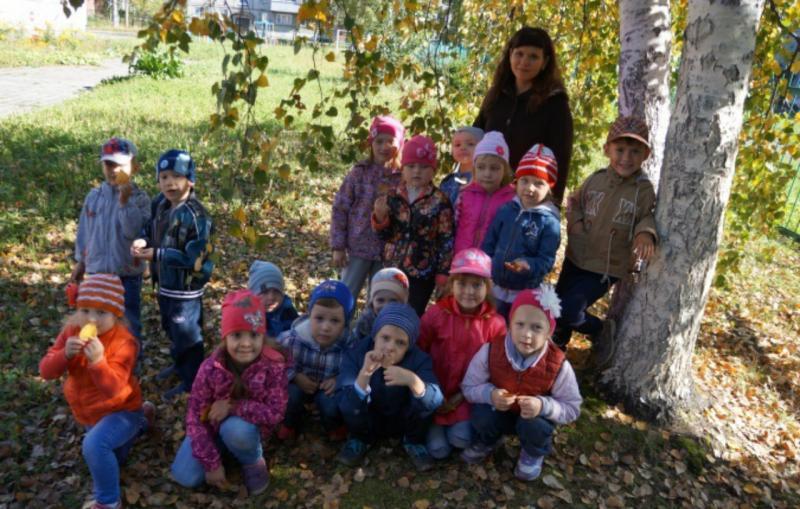 Воспитательница с детьми под осенним деревом