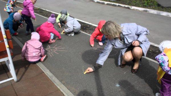 Воспитательница с детьми рисуют на асфальте