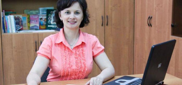 Воспитательница сидит за столом с блокнотом и ноутбуком