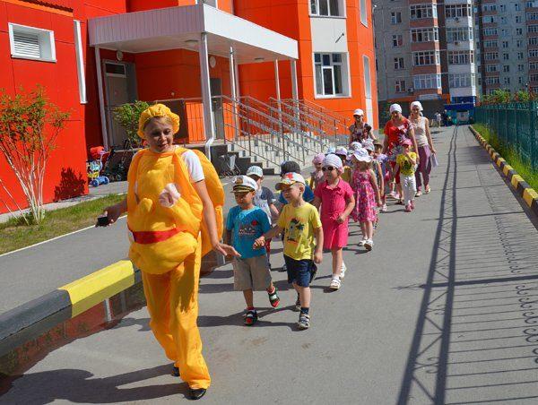 Воспитательница в жёлтом карнавальном костюме ведёт строй детей