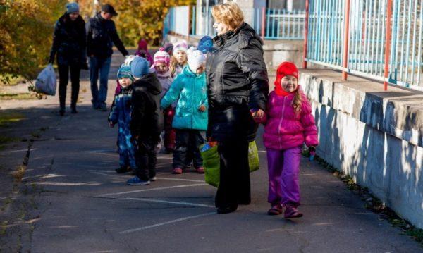 Воспитательница ведёт группу за территорией садика