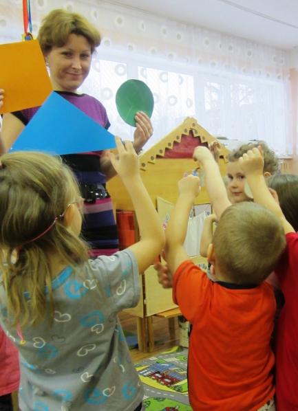 Воспитатель и дети держат в руках геометрические фигуры