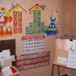 Уголок в виде домиков с буквами, кармашков с карточками и доской