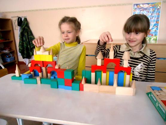 Две девочки строят замки с башнями из деревянных деталей