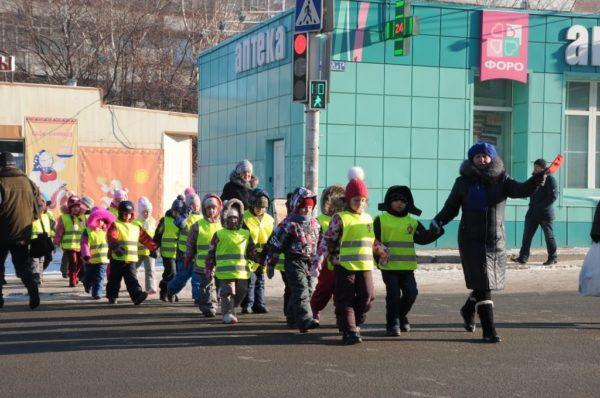Воспитатель переводит группу детей через дорогу по регулируемому пешеходному переходу