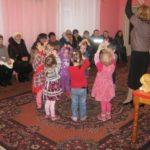 Дети и воспитатель стоят в кругу, подняв руки, родители наблюдают