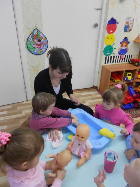 Дети и воспитатель купают кукол