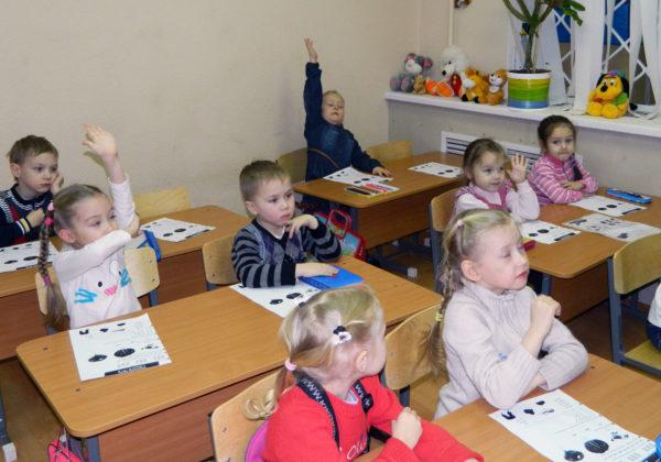 дети сидят за столами и занимаются