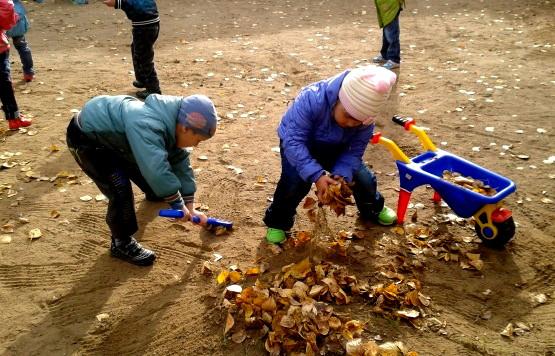 Дети убирают сухие листья во дворе