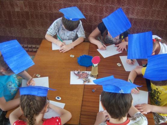 дети в бумажных профессорских шапочках