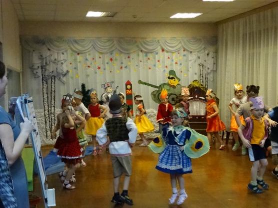 Дети в костюмах танцуют в зале