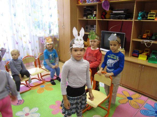 Дети в масках животных сидят на стульях, девочка-зайчик стоит на переднем плане
