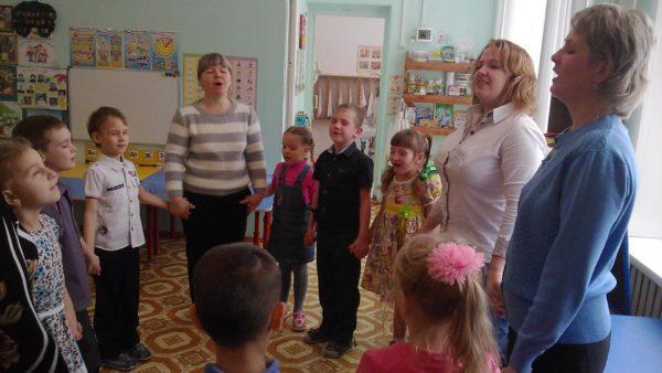 Дети, воспитательница и две мамы, взявшись за руки в хороводе, поют