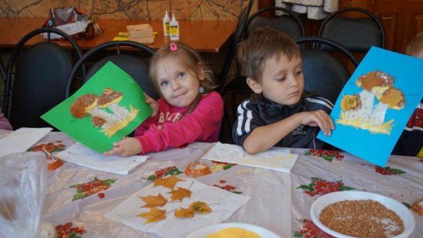 Девочка и мальчик сидят за столом и показывают аппликации с грибами