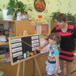 Девочка, стоя у доски рядом с воспитателем, называет буквы